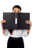 Woman hiding her face with a business file Stock Photo