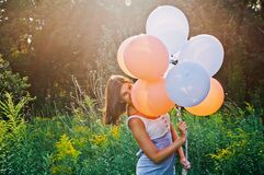 Woman hiding her smile behind colored baloons
