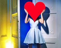 Woman hiding herself behind a heart Stock Photography