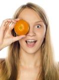 Woman hiding his eye with mandarin Stock Photo