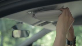 Woman hiding ignition key in car sun visor stock video footage