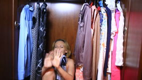 The woman is hiding inside the wardrobe. They found her, she is frightened and screams. Copy space left stock video footage