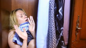 The woman is hiding inside the wardrobe. They found her, she is frightened and screams. Copy space left stock footage