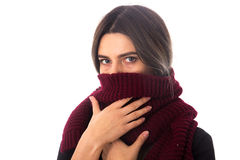 Woman hiding mouth under scarf. Young woman with dark hair in black blouse hiding her mouth under long vinous scarf on white background in studio Stock Images