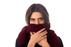 Woman hiding mouth under scarf. Young woman with dark hair in black shirt hiding her mouth under long vinous scarf on white background in studio Stock Photo