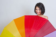 Woman hiding over colorful umbrella Stock Image