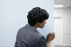 Woman hiding peering round corner Stock Photo
