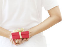 Woman hiding red gift box behind her back Royalty Free Stock Photography