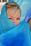 Woman hiding in silk. Pretty blonde haired woman hiding half her face behind a silk veil Royalty Free Stock Images