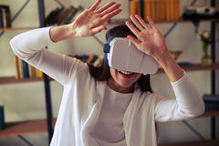 Woman hiding from something using hi-tech virtual reality headse Stock Image
