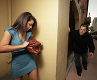 Woman hiding from the stalker. Young woman hiding behind a wall and looking for mace to fend off the thug about to victimize the woman stock photography