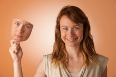Woman hiding under the happy mask. Hypocritical, insincere, two-faced female Stock Photos