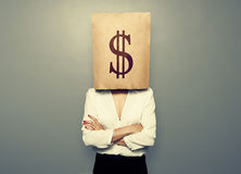 Woman hiding under paper bag with dollar sign Stock Photos