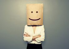 Woman hiding under smiley paper bag Stock Photography
