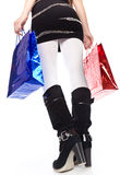 A woman in high boots keeps bright bags Royalty Free Stock Image