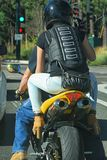 Woman in high heals on the back of a motor cycle with her shoes hooked to the foot rests. Dude driving bike stopped at red light with chick on the back in high Royalty Free Stock Images