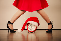 Woman in high heels with alarm clock. Christmas. Royalty Free Stock Photos