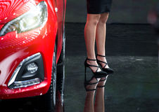 Woman with high heels beside car. Legs of attractive business woman in black skirt and high heels beside red modern car Royalty Free Stock Images