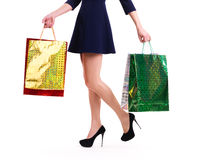 Woman in high heels with color shopping bags. Woman in high heels with color shopping bags standing -  isolated on white Royalty Free Stock Photography