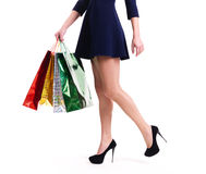 Woman in high heels with color shopping bags. Woman in high heels with color shopping bags standing -  isolated on white Royalty Free Stock Image