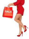 Woman on high heels holding shopping bags. Closeup picture of woman on high heels holding shopping bags Stock Photography