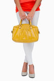 Woman in high heels holding yellow bag Stock Photos