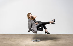 Woman in high heels posing in luxury office chair Stock Photography