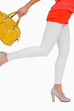 Woman in high heels rushing with yellow bag Stock Photography
