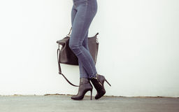 Woman in high heels shoes holds handbag Royalty Free Stock Photography