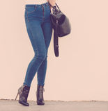 Woman in high heels shoes holds handbag Stock Photo