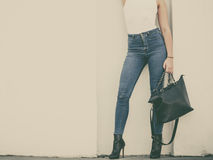 Woman in high heels shoes holds handbag Stock Photography