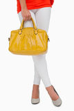 Woman in high heels standing with yellow bag Stock Photography