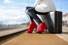 Woman in high heels at train station stock photography