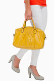 Woman in high heels walking with yellow bag Stock Image
