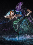 Woman High Kicking in Colorful Water Splashes Royalty Free Stock Photo