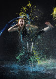 Woman High Kicking in Colorful Water Splashes Stock Photo