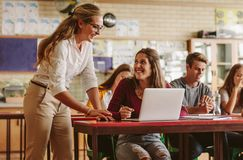 Woman high school professor helping student in class stock photography