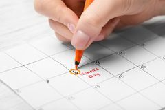 Woman highlighting date on calendar. Closeup. International Women's Day celebration Royalty Free Stock Images