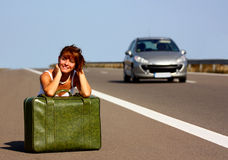 Woman on highway. Woman on a highway with a green briefcase and vehicle passing by Stock Photography