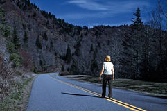 Woman on Highway on a Winter Night stock photo