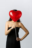 A woman higing behind a heart shaped balloon Royalty Free Stock Photos