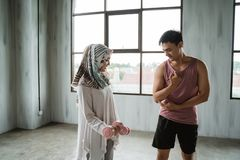 A woman hijab doing weight exercises with assistance of her personal trainer stock image