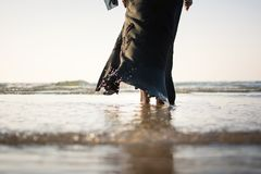 Woman in hijab standing on the beach. Back view Royalty Free Stock Images
