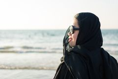 Woman in hijab standing on the beach. Woman in hijab at the beach standing by the water Stock Images