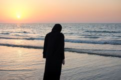 Woman in hijab standing on the beach. Looking at horizon Royalty Free Stock Photos