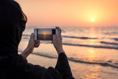 Woman in hijab taking picture of a sunset. On the beach Stock Image