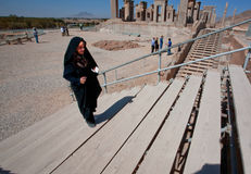 Woman in hijab traditional black dress walking on the Persepolis. PERSEPOLIS, IRAN: Woman in hijab traditional black dress walking on the Persepolis ruined city Royalty Free Stock Photos