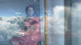 Woman with hijab typing on laptop. Side view of a mixed-race woman with hijab typing on laptop against connected lines and sky background stock footage