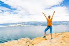 Woman hiker with arms outstretched, travel celebrating. Woman hiker hiking with backpack, arms outstretched looking at sea and mountains view. Accomplished royalty free stock images