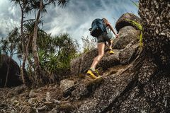 Woman hiker with backpack. Climbs steep rocky terrain royalty free stock photos